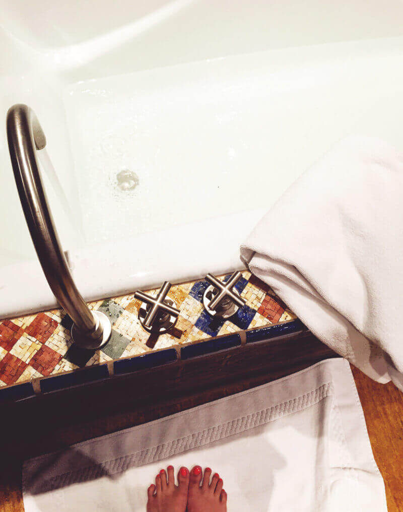 Using the bathtub at Inn of the Five Graces in Santa Fe, New Mexico